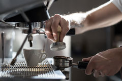 咖啡制造过程;浓咖啡杯子和咖啡机器; 库存照片