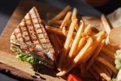 咖啡厅照相讲席会新的菜单,与鸡和菜的新鲜的三明治,莴苣沙拉、薯条和番茄酱 库存照片