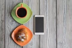 咖啡和一个新月形面包早餐在一张木桌上,一个手机紧挨着是 免版税库存照片