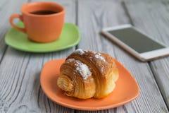 咖啡和一个新月形面包早餐在一张木桌上,一个手机紧挨着是 库存图片