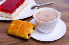咖啡和一个蛋糕在桌上在咖啡馆 免版税图库摄影