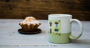 咖啡和一块杯形蛋糕在板材 库存照片