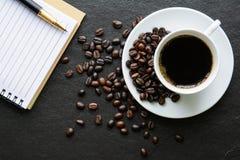 咖啡和一块笔记本和笔和玻璃在黑背景 库存照片