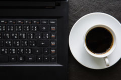 咖啡和一块笔记本和笔和玻璃在黑背景 库存图片