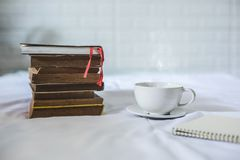 咖啡和一本书在床上 库存图片