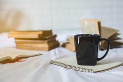 咖啡和一本书在床上 免版税库存图片
