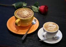 咖啡和一朵红色玫瑰在桌上 库存图片