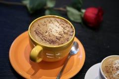 咖啡和一朵红色玫瑰在桌上 免版税库存图片