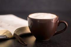 咖啡和一部圣经在板岩桌面 库存照片