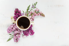 咖啡和不同的淡紫色花 免版税库存照片