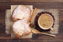咖啡和两个新鲜的小圆面包 图库摄影
