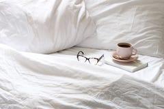 咖啡和书在床上 免版税库存图片
