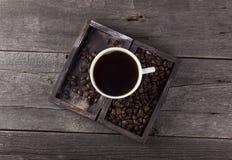 咖啡和咖啡粒在箱子在木背景 图库摄影