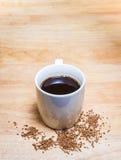 咖啡和咖啡粒子在木桌上 免版税图库摄影
