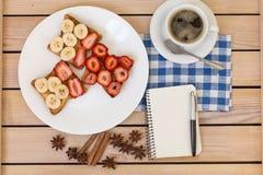 咖啡和多士用草莓和香蕉 记事本和笔 免版税库存图片