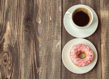 咖啡和多福饼在木背景 免版税库存照片