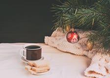 咖啡和奶蛋烘饼在板材 在圣诞树的圣诞节装饰 免版税库存照片
