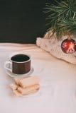 咖啡和奶蛋烘饼在板材 在圣诞树的圣诞节装饰 免版税库存图片