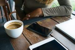 咖啡和妇女咖啡馆的与手机,笔记薄, lapto 免版税库存照片