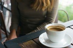 咖啡和弄脏坐在咖啡店的妇女 免版税库存照片