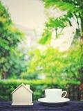 咖啡和微型木屋在木桌上有绿色庭院背景 库存图片