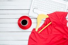 咖啡和挂衣架与红色礼服在计算机附近 库存照片