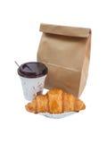 咖啡和新月形面包与被隔绝的纸袋 库存照片