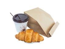 咖啡和新月形面包与被隔绝的纸袋 库存图片