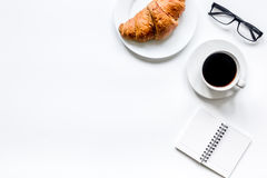咖啡和新月形面包商人白色办公桌背景顶视图空间早餐文本的 免版税库存照片