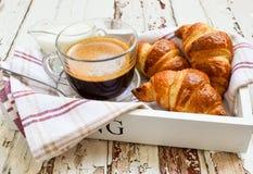 咖啡和新月形面包在木盘子 库存照片
