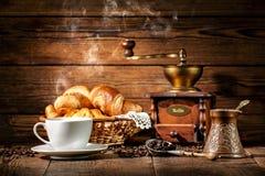 咖啡和新月形面包在木背景 免版税库存图片