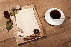 咖啡和曲奇饼与老纸片在木背景、香料和装饰,顶视图,减速火箭的样式 库存图片
