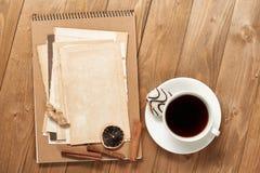 咖啡和曲奇饼与老纸片在木背景、香料和装饰,顶视图,减速火箭的样式 库存照片