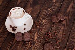 咖啡和曲奇饼在一张木桌上的Oreo 图库摄影