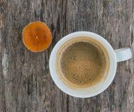咖啡和杯形蛋糕在黑暗的木背景 免版税库存图片