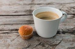 咖啡和杯形蛋糕黑暗的木表面上 库存图片