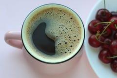 咖啡和樱桃 Minimalistic概念,在白色板材的红色樱桃 r 库存图片