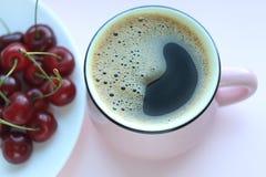 咖啡和樱桃 Minimalistic概念,在白色板材的红色樱桃 r 库存照片