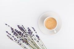 咖啡和淡紫色在白色桌上从上面开花 妇女运转的书桌 舒适早餐大模型 平的位置样式 免版税库存照片