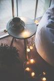 咖啡和温暖的圣诞灯在桌上 免版税库存图片