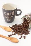 咖啡和溢出的咖啡豆从玻璃瓶子 免版税库存图片