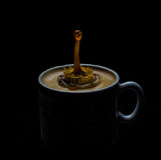 咖啡和牛奶飞溅在白色杯子 库存照片
