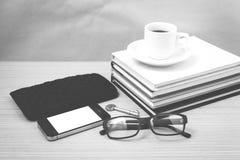 咖啡和电话有堆的书、钥匙、镜片和钱包bl 免版税图库摄影
