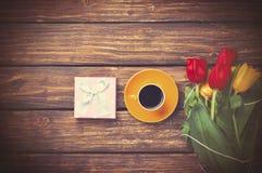 咖啡和礼物在郁金香附近在木背景 免版税库存图片