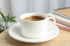 咖啡和笔记本在木桌上反对轻的背景与植物,空间文本的 库存照片