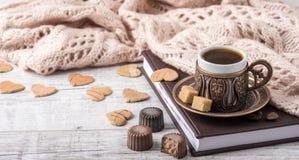 咖啡和笔记本有一条被编织的围巾的在桌上 免版税库存图片