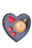 咖啡和糖果在一个盘子以心脏的形式,被隔绝 免版税库存图片