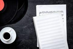 咖啡和纪录与纸笔记在音乐演播室dj或音乐家工作的在黑暗的背景顶视图大模型 库存照片