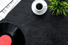 咖啡和纪录与纸笔记在音乐演播室dj或音乐家工作的在黑暗的背景顶视图大模型 免版税库存照片