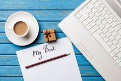 咖啡和纸与我的书题字在笔记本附近 免版税库存照片